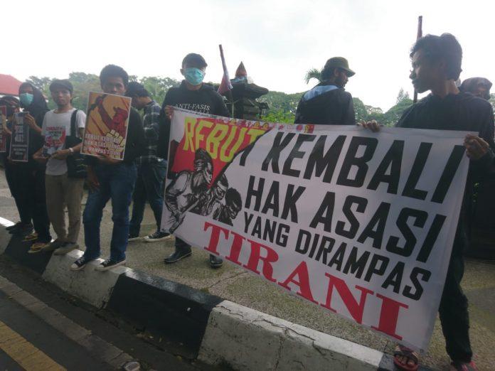 Massa aksi Aliansi Perjuangan Demokrasi melakukan unjuk rasa peringati HAM internasional di depan gedung DPRD Kota Malang